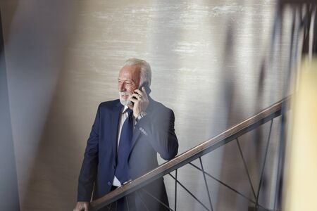 Senior businessman standing on modern office building staircase, having a phone conversation