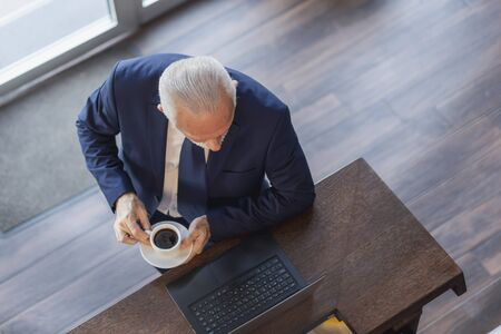 High angle view portrait of a senior businessman standing by a restaurant counter, drinking coffee and working on a laptop computer Stockfoto