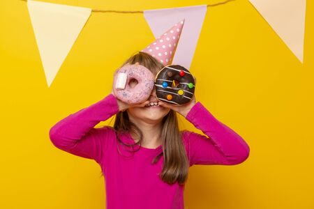 Beautiful little girl wearing birthday hat, holding colorful donuts as glasses and peeking, isolated on yellow colored background with party flags