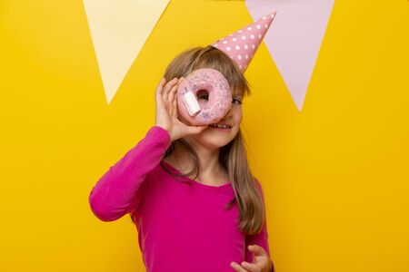 Beautiful little girl wearing birthday hat, having fun holding donut and peeking, isolated on yellow colored background with party flags