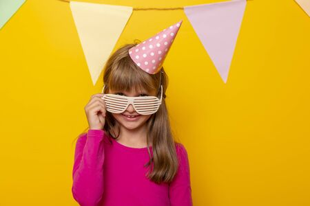 Portrait of a beautiful little girl wearing party glasses and birthday hat, having fun celebrating her birthday, isolated on yellow colored background