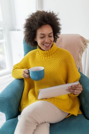 Beautiful woman sitting in an armchair, having a video call on a tablet computer and drinking tea; woman enjoying her leisure time activities at home Stockfoto