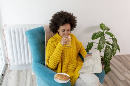 Beautiful mixed race woman relaxing at home, sitting in an armchair, reading newspapers and having breakfast