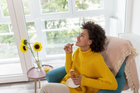 Beautiful mixed race woman relaxing at home, sitting in an armchair and eating a fresh croissant for breakfast