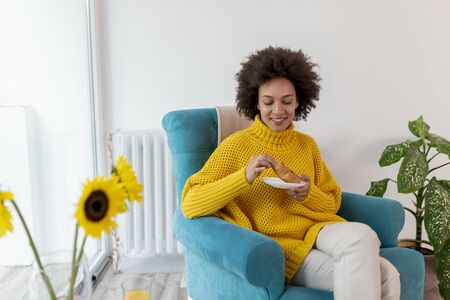 Beautiful mixed race woman relaxing at home, sitting in an armchair and having breakfast Stockfoto
