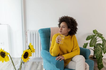 Beautiful mixed race woman relaxing at home, sitting in an armchair and drinking orange juice for breakfast