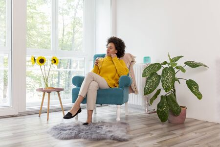Beautiful mixed race woman relaxing at home, sitting in an armchair and drinking orange juice for breakfast Stockfoto - 137854324