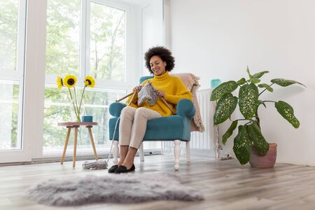 Beautiful young mixed race woman sitting in an armchair,  knitting a scarf and relaxing at home Stockfoto