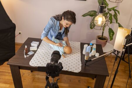 Female vlogger recording video about newborn baby oral cavity care; influencer making video about cleaning newborn baby mouth as part of online prenatal classes Stockfoto