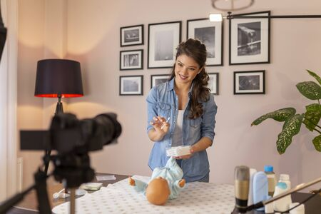 Female vloger recording video about cleaning newborn baby ears with safety cotton ear buds as part of online prenatal classes Stockfoto