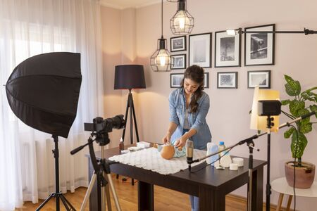 Female vlogger filming video about changing newborn baby clothes as part of online prenatal classes course; female influencer recording tutorial about newborn baby care Stockfoto - 137854334