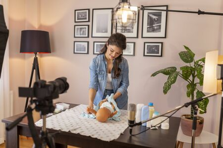 Female vlogger filming video about changing newborn baby clothes as part of online prenatal classes course; female influencer recording tutorial about newborn baby care Stockfoto