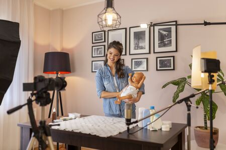 Female vlogger recording video about double diapering and newborn baby proper hip positioning to prevent hip dysplasia as part of online prenatal classes