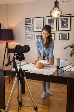 Female vlogger filming video about double diapering and newborn baby proper hip positioning to prevent hip dysplasia as part of online prenatal classes