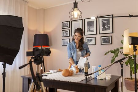 Female vlogger filming video about double diapering and positioning newborn baby hips to prevent hip dysplasia as part of online prenatal classes