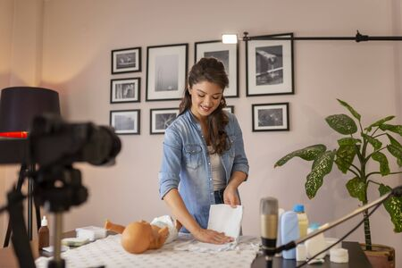 Female vlogger filming video about double diapering and positioning newborn baby hips to prevent hip dysplasia as part of online prenatal classes Stockfoto - 137854352
