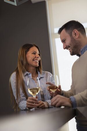 Beautiful couple in love on a date, standing next to a restaurant counter, drinking wine and having a pleasant conversation