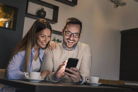 Beautiful young couple sitting at a restaurant table, drinking coffee and using a smartphone Stockfoto - 137889817