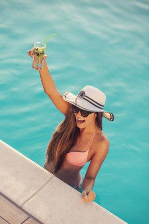 Attractive young woman wearing bikini, sunglasses and a hat, standing in the swimming pool next to the edge, drinking cocktails and dancing
