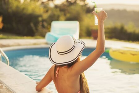 Attractive young woman wearing bikini and a hat, standing in the swimming pool, enjoying beautiful summer sunset, looking away from the camera Stockfoto - 137889829