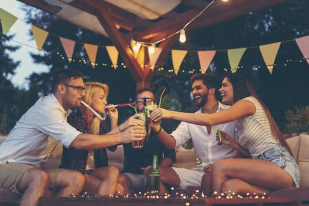 Group of young friends blowing party whistles, making a toast and having fun at an outdoor summertime party
