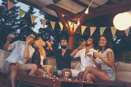 Group of young friends blowing party whistles, drinking beer and having fun at an outdoor summertime party Stockfoto