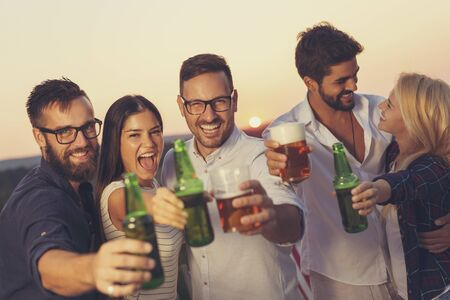 Group of friends at a summertime outdoor party having fun, dancing, drinking beer and making a toast Stockfoto - 137890311