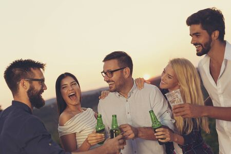 Group of friends at a summertime outdoor party having fun, dancing, drinking beer and making a toast