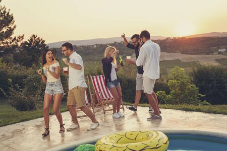 Group of friends having fun at a summertime poolside party, dancing and drinking beer