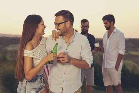Couple in love having fun at an outdoor summertime party, making a toast and drinking beer