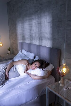 Portrait of a beautiful pregnant woman wearing nightgown, lying in bed and relaxing at home Stockfoto