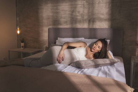 Portrait of a beautiful pregnant woman wearing nightgown, lying in bed and relaxing at home Stok Fotoğraf - 137892098