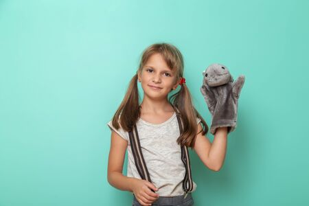 Portrait of a beautiful little girl playing with a hippo puppet isolated on mint colored background
