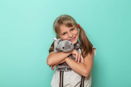Portrait of a beautiful little girl hugging her favourite isolated on mint colored background