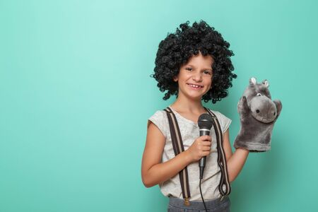 Portrait of child comedian performing with a puppet, isolated on mint colored background