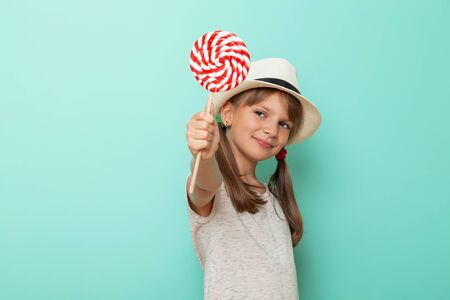 Portrait of a beautiful little girl wearing summer hat and holding colorful lollipop isolated on mint colored background Stockfoto