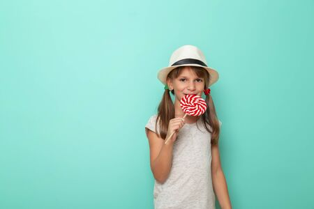 Portrait of a beautiful little girl wearing summer hat and eating colorful lollipop isolated on mint colored background Stockfoto