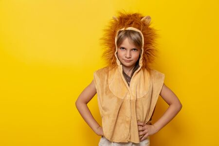 Beautiful little girl wearing lion carnival costume isolated on yellow colored background Stockfoto
