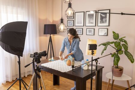 Healthcare specialist filming video about newborn baby scratching protection as part of online prenatal classes course; female influencer recording tutorial about newborn baby care 免版税图像