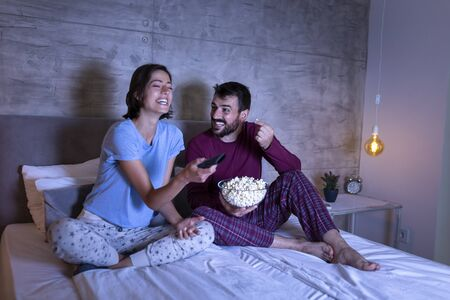 Couple in love lying in bed, eating popcorn and watching a movie, relaxing at home at night