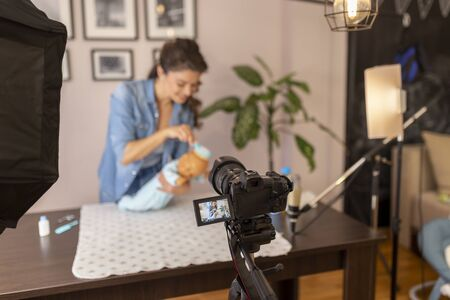 Female vlogger making a video about brushing newborn baby hair, parietal region and soft spot care as a part of online antenatal classes course 免版税图像