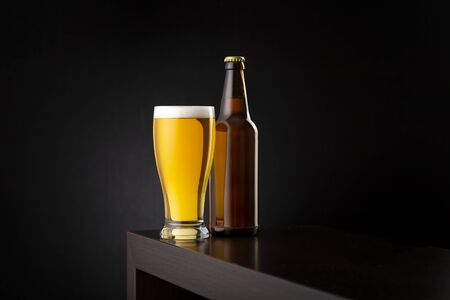 Glass of cold pale beer and a beer bottle placed on a bar counter with copy space