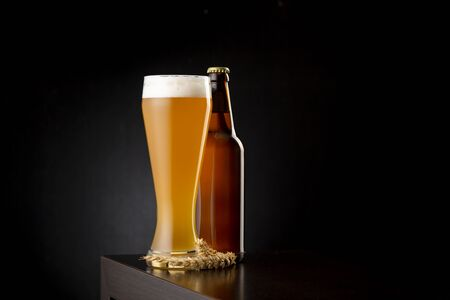Glass of cold unfiltered wheat beer and a beer bottle on a bar counter with copy space Stock Photo