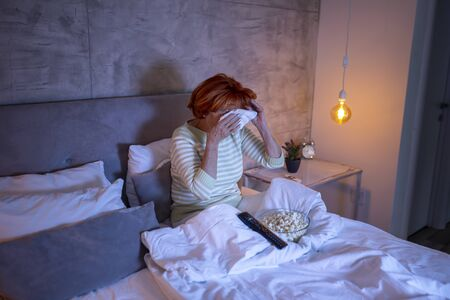 Senior woman wearing pajamas sitting on bed, watching drama movie on TV, sad, crying and wiping tears with a handkerchief