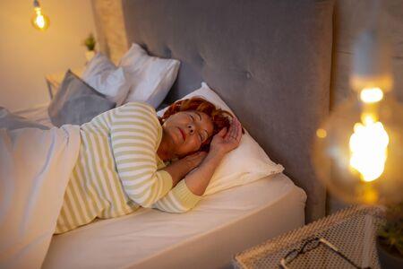 Senior woman wearing pajamas lying in bed, sleeping in bedroom Imagens