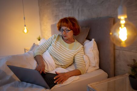 Portrait of senior woman wearing pajamas lying in bed at night, working late using a laptop computer Imagens
