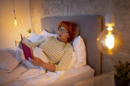 Elderly woman wearing pajamas lying in bed, relaxing at home in the evening, reading a book