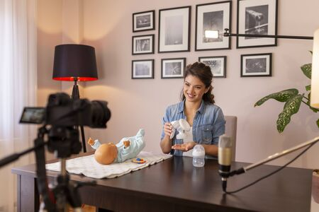 Female vlogger recording tutorial about pump use instructions as part of online prenatal classes course 免版税图像