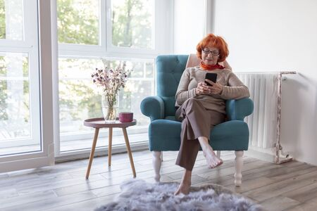 Senior woman enjoying her leisure time at home, sitting in an armchair and typing a text message using a smart phone 版權商用圖片