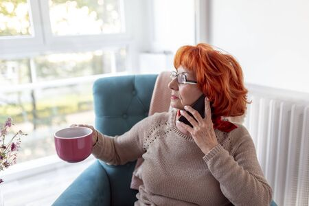 Beautiful senior woman relaxing at home, sitting in an armchair, drinking tea and having a phone conversation